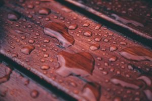 Rain drops collect on brownish red wood