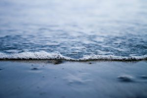 Foam from gentle waves glides over sand